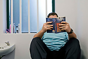 A prisoner reading a book in his cell. HMP Wandsworth, London, United Kingdom