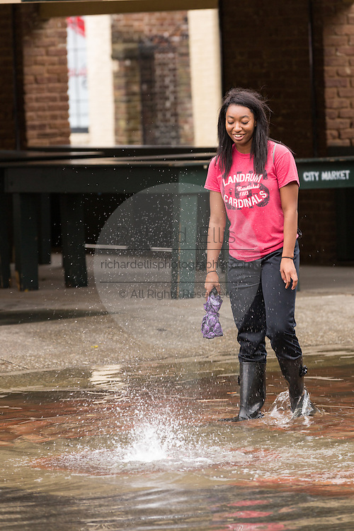 A College of Charleston student watches water bubble up from a manhole drain as severe flooding continued for the second day in the historic district as Hurricane Joaquin brings heavy rain, flooding and strong winds as it passes offshore October 4, 2015 in Charleston, South Carolina.