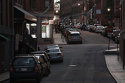 Portland Maine, Market Street. Streetscape at Dusk on a Friday Night in early June 2011. Shop windows lit warm glow, blue cast to street and brick sidewalks.