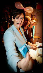 Prime minister's wife Cherie Blair offers a photographer a condom as she tours the exhibition stands in the conference centre in Brighton during the Labour Party conference today 28 September 2005. PA Photo: Andrew Parsons.