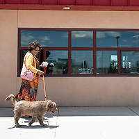 Cindy Dayish, a staff member at Navajo Technical University (NTU) walks her rescue dog Coco in front of the Wellness Center Wednesday, June 19 during take your dog to work week at NTU.