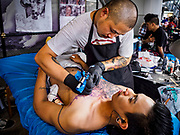 28 OCTOBER 2018 - BANGKOK, THAILAND: A man gets a tattoo on his chest at the 2018 MBK Center Tattoo Fest. Tatoo artists from around the world came to participate in the festival, which featured both modern (using tattoo machines) and traditional methods (done by hand with long needles) of tattooing.      PHOTO BY JACK KURTZ