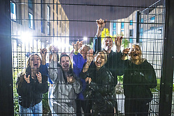 © Licensed to London News Pictures. 26/09/2020. Manchester, UK. Several first year students pose for a photo from behind fencing at the perimeter of the campus . Students at Manchester Metropolitan University ( MMU ) have been told to isolate within their Halls of Residence for fourteen days after several Coronavirus outbreaks have been identified across the campus . Several report being denied permission to move to and from the University campus , enforced by security guards , saying they have been told that, if they step outside , they will not be able to return for at least 14 days . Photo credit: Joel Goodman/LNP