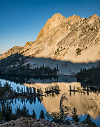 The peak of El Capitan (9901 feet or 3018 m elevation) reflects in Alice Lake in Sawtooth Wilderness, Blaine County, Idaho, USA. On October 6-7, 2020, starting from Tin Cup Trailhead, I hiked the Alice-Toxaway Loop clockwise for 20 miles including an overnight stay at idyllic Twin Lakes. The first day to Twin Lakes was a moderate 7.4 miles with 2090 feet gain. The second day returned via Toxaway Lake and Farley Lake for 12.5 miles with 1260 feet up and 2940 feet down. For the most dramatic scenic build-up, I recommend backpacking 3 days counterclockwise staying at Toxaway Lake then Twin Lakes. (On a 2007 backpacking trip in August, we enjoyed staying 2 nights at Alice Lake and day-hiked to Toxaway.) The Sawtooth Range (part of the Rocky Mountains) are made of pink granite of the 50 million year old Sawtooth batholith. This image was stitched from multiple overlapping photos.