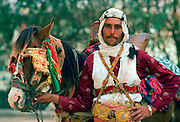 Horseman in traditional dress with horse with eye defenders against the sun and dust
