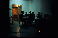 A group of men talking together at night in a Miao Village, Guizhou Province, China.
