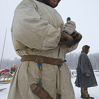 North of the Arctic Circle in Russia, a nomadic Komi reindeer herder displays his knife scabbard that hangs from a traditional decorated belt.  Behind him, a woman stands in a malitsa robe and reindeer skin mukluks.