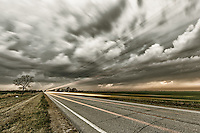 Traffic blows by as the winds from a nearby supercell thunderstorm blow across Kansas