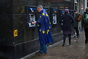 Man supporting the Remain campaign and wearing the European flag draws cash from a London bank cash dispenser before the Together for the final say march for a People¹s Vote on 19th October 2019 in London, United Kingdom. On this day parliament will be sitting on a Saturday for the first time since the 1980s, as time runs out before the PM is supposed to ask the EU for a three month extension by law under the Benn Act. With less than two weeks until the UK is supposed to be leaving the European Union, the final result still hangs in the balance and protesters gathered in their hundreds of thousands to make political leaders take notice and to give the British public a vote on the final Brexit deal, with the aim to revoke Article 50.