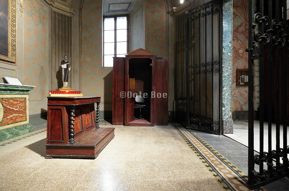 confessional in side chapel of a large church Italy
