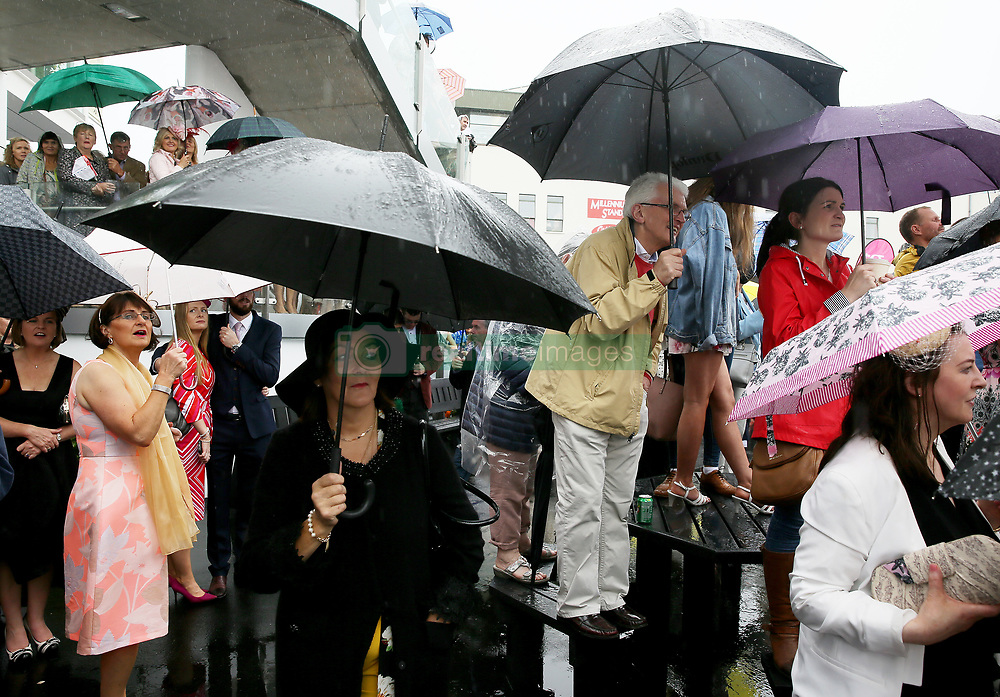 Racegoers shelter from the rain whilst watching the judging for Ladies Day during day four of the Galway Summer Festival at Galway Racecourse.