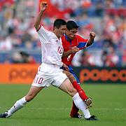 China's Haidong Hao battles with Costa Rica's Mauricio Solis