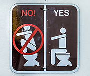 YES/NO! sign illustrating proper use of a western-style toilet (no squatting). Grand Teton National Park, Wyoming, USA.