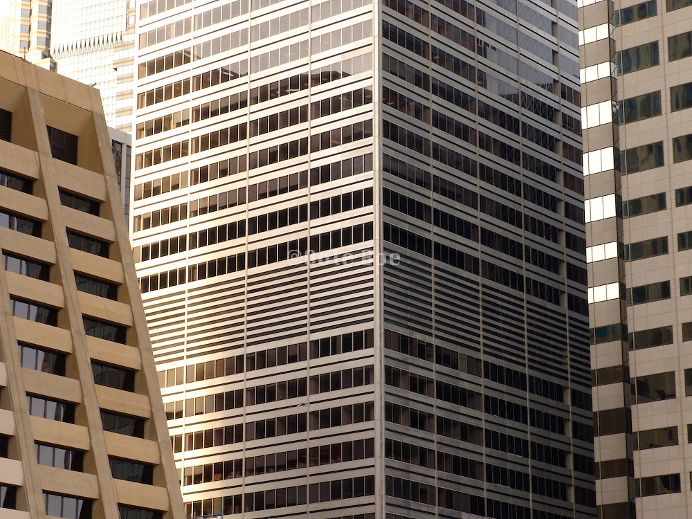 Three high rise buildings standing close to each other.