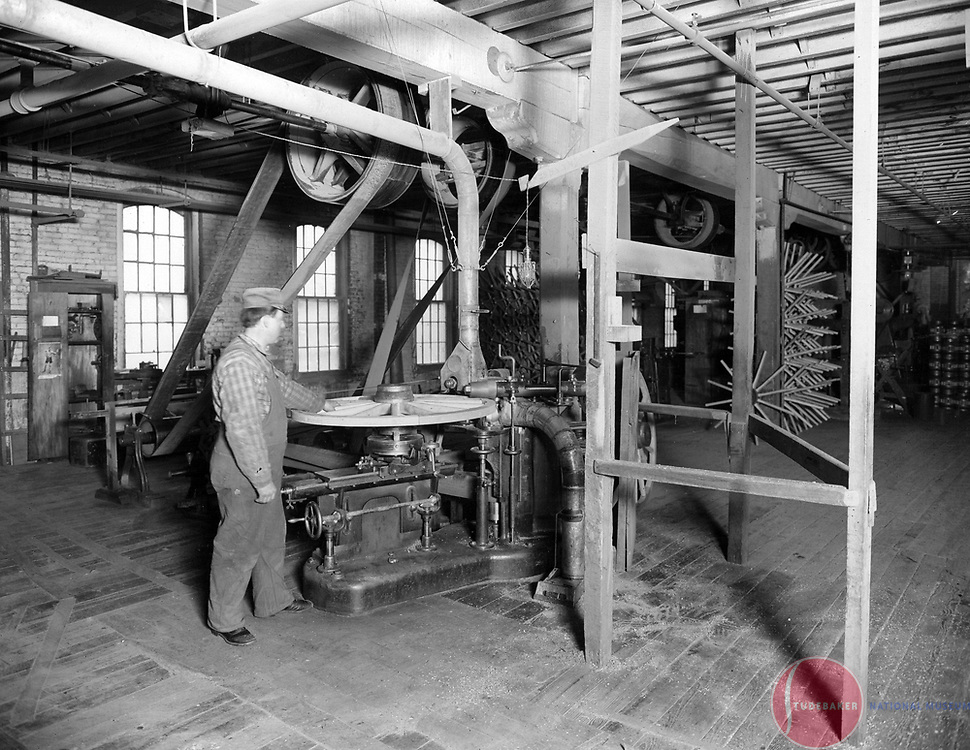 A Studebaker worker trues up a wagon wheel in this c. 1900 image.
