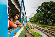 05 JUNE 2014 - YANGON, YANGON REGION, MYANMAR: Passengers on the Yangon Circular Train. The Yangon Circular Train is a commuter train that circles Yangon, Myanmar (Rangoon, Burma). The train is 45 kilometers long, makes 38 stops and takes about three hours to make a loop of the city.     PHOTO BY JACK KURTZ