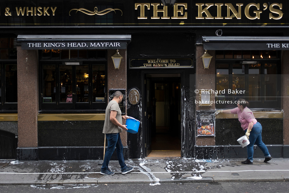 With a further 89 UK covid victims in the last 24hrs, bringing the total victims to 43,995 during the Coronavirus pandemic, pubs, restaurants and hairdressers will be able to reopen on 4th July, providing they adhere to COVID Secure guidelines. Two employees use buckets of soapy water to wash the exterior of the King's Head pub in Mayfair, on 2nd July 2020, in London, England.