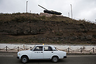 A taxi drives past a T-72 tank that now stands as a memorial as one enters the town of Shushi in Nagorno-Karabakh. In May 1992 the tank was part of the successful Armenian attack on the Azeri-held city; it was hit and two of its crew killed. In 1991 Nagorno-Karabakh broke away from Azerbaijan, declaring independence. Internationally, however, it is still recognized as part of Azerbaijan.