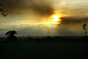 Smoke from a farm fire near Burton Latimer partly obscures the sun as it sets over kettering, northamptonshire