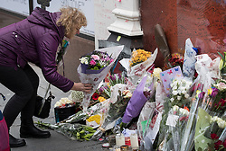 © Licensed to London News Pictures. 10/01/2017. London, UK. A fan places flowers at a mural and shrine to David Bowie in Brixton on the first anniversary of his death. David Bowie was born in Brixton, south London. Photo credit: Peter Macdiarmid/LNP