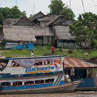 A heavily-laden boat carrying passengers and cargo up the Peruvian Amazon River stops by a floating stores at a village.