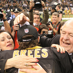16 January 2010:  New Orleans Saints owner Tom Benson (right) and his wife Gayle Benson (left) hug quarterback Drew Brees (9) following a 45-14 win by the New Orleans Saints over the Arizona Cardinals in the 2010 NFC Divisional Playoff game at the Louisiana Superdome in New Orleans, Louisiana.