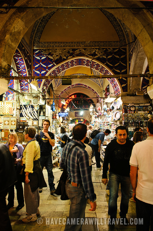 A bustling street inside Istanbul's historic Grand Bazaar. The bazaar's streets are all covered, with the ceilings often ornately painted.