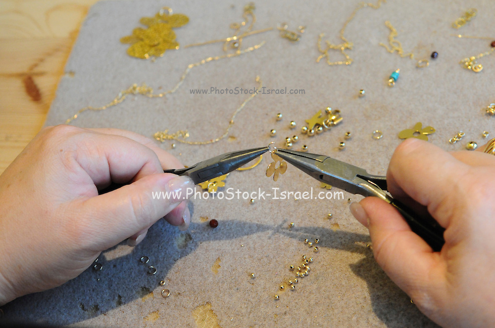 hand of a jeweler holding long nosed pliers to make earrings