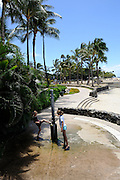 2 children (8 years old, 11 years old) using open-air shower on Waikiki Beach, Waikiki, Honolulu, Hawaii
