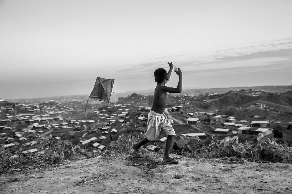 A boy is playing with a handmade kite above the Twangkhali camp. Since the end of august 2017, the beginning of the crisis, more than 600,000 Rohingyas have fled Myanmar to seek refuge in Bangladesh. Cox's Bazar - 3 november 2017.<br /> Un garçon joue avec un cerf-volant fait main sur les hauteurs du amp de Twangkhali. Depuis le début de la crise, fin août 2017, plus de 600000 Rohingyas ont fuit la Birmanie pour trouver refuge au Bangladesh. Cox's Bazar le 3 novembre 2017.