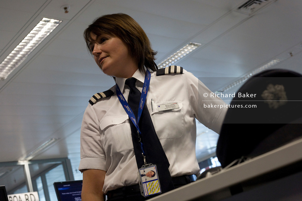 A lady pilot examines flight data and documents in the British Airways Crew Report Centre at Heathrow Airport's T5