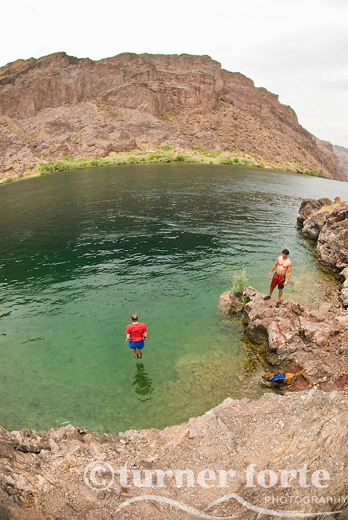 Adventurers jump off a cliff in The Black Canyon, Nevada.