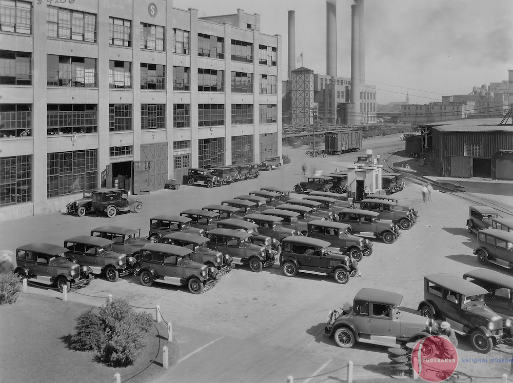 New 1926 Studebaker automobiles sit outside of building #78.  Studebaker's power plant is visible in the background (smokestacks.)