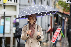© Licensed to London News Pictures. 13/05/2021. London, UK. A woman wearing a face covering shelters from rain beneath an umbrella in north London. It has been reported that government officials are discussing ending coronavirus face covering rules and only making masks mandatory on public transport by the end of June. The next stage of the Covid-19 lockdown easing takes place from Monday 17 May, allowing people to hug and return to mixing indoors in pubs and restaurants. Photo credit: Dinendra Haria/LNP