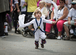 © Licensed to London News Pictures. 23/08/2015 . Uppermill , Saddleworth , Greater Manchester , UK. <br /> The Saddleworth Ruschart Festival in Uppermill today (Sunday 23rd Aug 2015).<br /> A rushcart built of moorland rushes is pulled by Morris Dancers from Uppermill village square to St Chad's Church.  The tradition arises from the laying of rushes on the church floor to keep it warm in winter.<br /> Will Arrowsmith , 22 months , from Sheffield has a go at Morris Dancing.<br /> <br /> Photo credit : Chris Bull / LNP