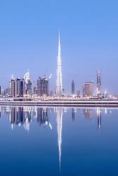 Skyline of skyscrapers and Burj Khalifa tower before sunrise in Dubai United Arab Emirates