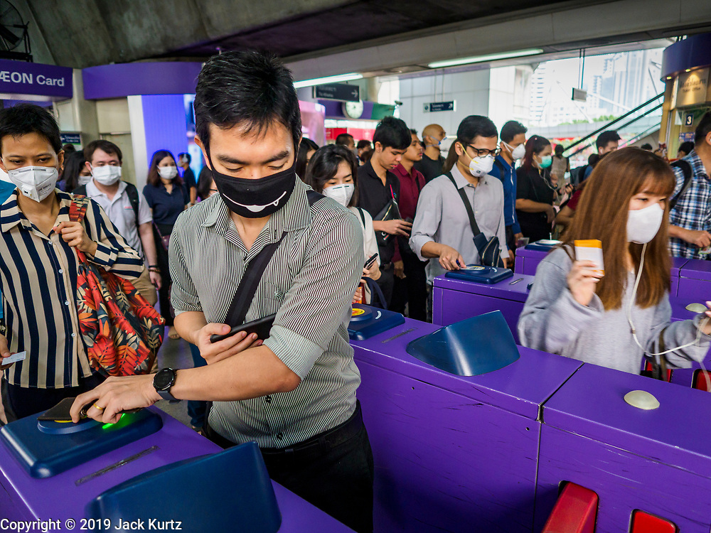 31 JANUARY 2019 - BANGKOK, THAILAND:   Morning commuters wearing breathing masks because of the air pollution over Bangkok leave the Asok BTS Skytrain station. The Thai government has closed more than 400 schools for the rest of the week because of high levels of pollution in Bangkok. At one point Wednesday, Bangkok had the third highest level of air pollution in the world, only Delhi, India and Lahore, Pakistan were worst. The Thai government has suspended some government construction projects and ordered other projects to take dust abatement measures. Bangkok authorities have also sprayed water into the air in especially polluted intersections to control dust. Bangkok's AQI (Air Quality Index) Thursday morning was 180, which is considered unhealthy for all people.    PHOTO BY JACK KURTZ