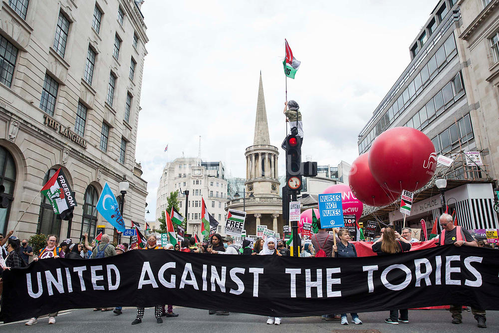 Thousands of people attend a United Against The Tories national demonstration organised by the Peoples Assembly Against Austerity in protest against the policies of Prime Minister Boris Johnsons Conservative government on 26th June 2021 in London, United Kingdom. The demonstration contained blocs from organisations and groups including Palestine Solidarity Campaign, Stand Up To Racism, Stop The War Coalition, Extinction Rebellion, Kill The Bill and Black Lives Matter as well as from trade unions Unite and the CWU.