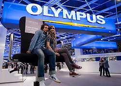 visitors posing for photograph at Olympus stand at Photokina digital imaging trade show in Cologne Germany 2010