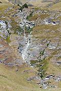 Series of waterfalls cascading down a cliff near the Treble Cone ski field, outside Wanaka, New Zealand.