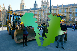 © Licensed to London News Pictures.  04/10/2012. LONDON, UK. Oxfam employees pose with a map of Africa split down the middle outside the Houses of Parliament to highlight the problem of land grabs. The charity calculates that an area of the size of London is sold to foreign investors every six days in the poorest countries on earth driving up food prices. Photo credit :  Cliff Hide/LNP