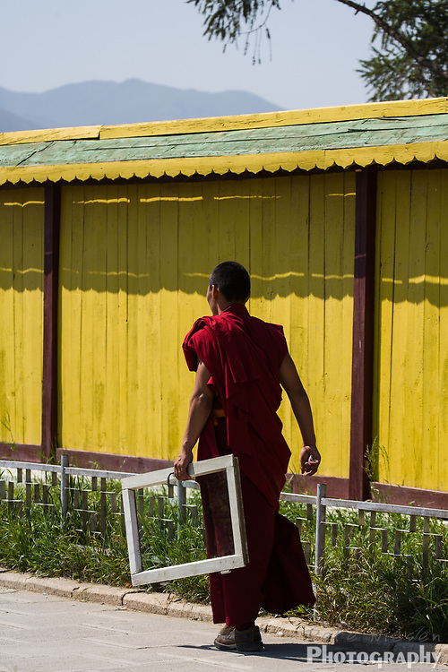 Budhist monk in red robes carrying a window frame
