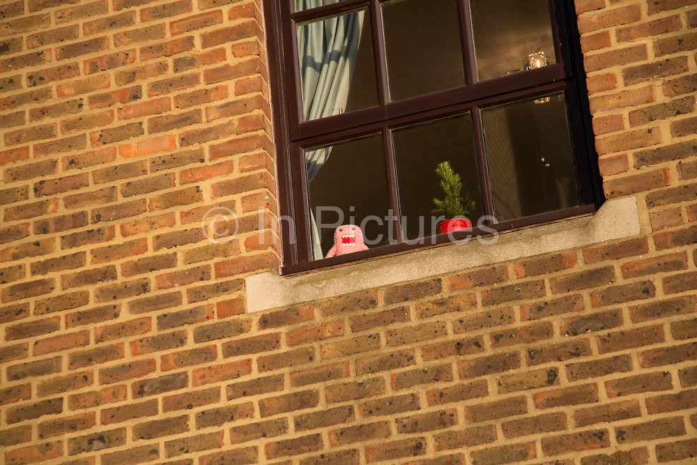 Soft toy character peering out of a top floor window as if trapped inside. London, UK.