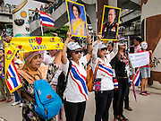 "14 JULY 2013 - BANGKOK, THAILAND:  Thai White Mask protesters hold up pictures of Bhumibol Adulyadej, the King of Thailand, (right) and his wife, Queen Sirikit during a White Mask protest. About 150 members of the so called ""White Mask"" movement marched through the central shopping district of Bangkok Sunday to call for the resignation of Yingluck Shinawatra, the Prime Minister of Thailand. The White Mask protesters are strong supporters of the Thai monarchy. They claim that Yingluck is acting as a puppet for her brother, former Prime Minister Thaksin Shinawatra, who was deposed by a military coup in 2006 and now lives in exile in Dubai.       PHOTO BY JACK KURTZ"