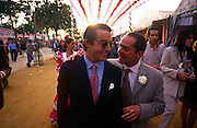 Two Spanish men walk and talk during the Spring Feria in Seville, Spain. Crowds of locals mingle in the late-afternoon sunshine at this lively event that Seville holds annually in the vast fairground area on the far bank of the Guadalquivir River. Rows of temporary marquee tents, or casetas, host families, corporations and friends into the late hours during the April Fair which begins begins two weeks after the Semana Santa, or Easter Holy Week in the Andalusian capital.