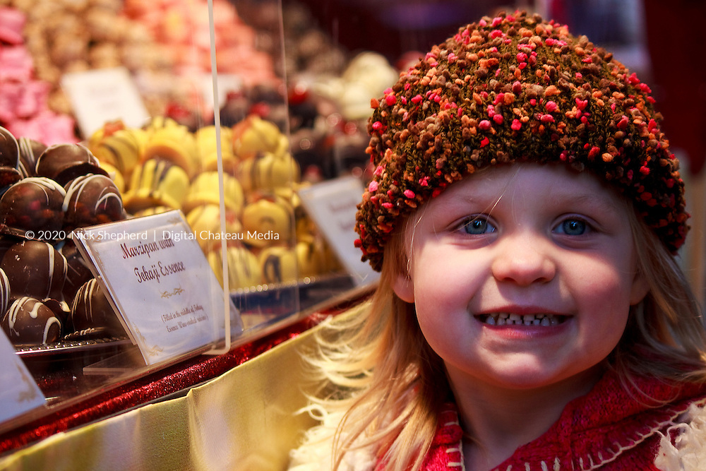 A young european girl wearing a woolly hat, smiling with excitement and joy after looking in a sweet shop window.