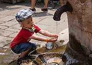A girl washes hands at well faucet, in Venice, Italy, Europe. Because Venice was cut off from reliable sources of fresh water, Venetians built underground clay-lined cisterns to collect and filter rainwater. Many wellheads were decorated with carvings of saints, family crests, inscriptions in Carolingian, Byzantine, Gothic, Renaissance, and Baroque era styles. An aqueduct from the mainland completed in the late 1800s made most wells obsolete. Venezia, founded in the 400s AD, is capital of Italy's Veneto region, named for the ancient Veneti people from the 900s BC. The romantic City of Canals stretches across 100+ small islands in the marshy Venetian Lagoon along the Adriatic Sea, between the mouths of the Po and Piave Rivers. The Republic of Venice was a major maritime power during the Middle Ages and Renaissance, a staging area for the Crusades, and a major center of art and commerce (silk, grain and spice trade) from the 1200s to 1600s. The wealthy legacy of Venice stands today in a rich architecture combining Gothic, Byzantine, and Arab styles. Venice and the Venetian Lagoon are honored on UNESCO's World Heritage List.