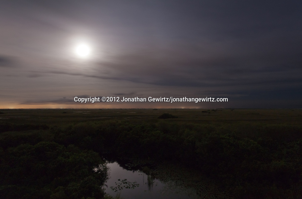 The full moon shines through an overcast night sky to illuminate a pond and sawgrass prairie in the Shark Valley section of Everglades National Park, Florida. WATERMARKS WILL NOT APPEAR ON PRINTS OR LICENSED IMAGES.