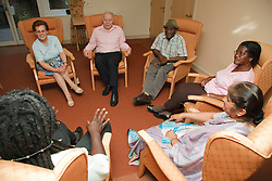 Social worker with multiracial group of older people in Residential home.