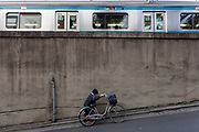 An older Japanese woman pushes her bicycle up a slope by Nishi Nippori station.Tokyo, Japan. Friday March 19th 2021